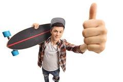 Den tonårs- skateboradåkaren med en longboard som gör en tumme gör en gest upp royaltyfri bild
