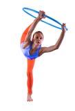 Den tonårs- sportive flickan gör övningar med hulabeslag t på grå bakgrund Ha gyckel som spelar leken Sund livsstil Co för sport Royaltyfria Bilder