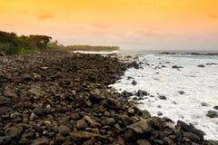 Den tonade härliga rosa färgen vinkar avbrott på en stenig strand på soluppgång på ostkust av den stora ön av Hawaii Fotografering för Bildbyråer