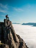 Den tonade vuxna kvinnan för bilden med en ryggsäck står på kanten av en klippa och att se soluppgången mot den blåa himlen Arkivbilder