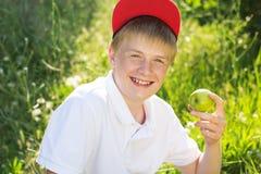 Den tonåriga blonda pojken rymmer gröna äpplen Arkivfoton
