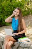Den tonåriga flickan arbetar med bärbara datorn i hörlurar och böcker Arkivfoto