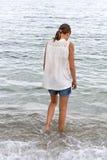 Den tonåriga flickan går in i havet Royaltyfri Bild