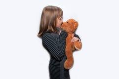 Den tonåriga flickan kysser leksakbjörnen Fotografering för Bildbyråer