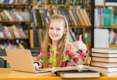 Den tonåriga flickan med bärbara datorn i arkivvisning tummar upp Royaltyfria Bilder