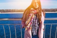 Den tonåriga lyckliga flickan kopplar av nära floden i stad parkerar utomhus- Royaltyfri Foto