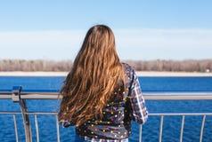 Den tonåriga lyckliga flickan kopplar av nära floden i stad parkerar utomhus- Royaltyfri Bild
