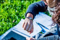 Den tonårs- flickan som ser hennes nära handklocka - se tiden - sköt upp Royaltyfri Foto