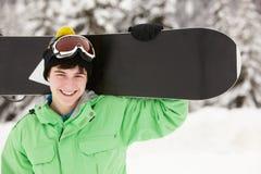 Den tonårs- pojken med snowboarden skidar på ferie Arkivbild