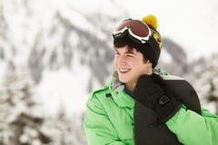 Den tonårs- pojken med snowboarden skidar på ferie Arkivfoto