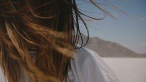 Den toppna närbildlivsstilståenden av den lyckliga unga kvinnan som ler på kameran med flyghår och hänglsen på, saltar ökensjön arkivfilmer