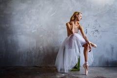 Den toppna slanka ballerina i en svart klänning poserar i studion Arkivbilder