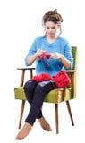 Den torterade unga flickan i en tröja sitter på en stol med ett rött garnnystan och att sticka en halsduk och en Spitz trött Vit  Royaltyfria Foton
