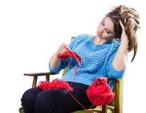 Den torterade unga flickan i en tröja sitter på en stol med ett rött garnnystan och att sticka en halsduk och en Spitz trött Vit  Arkivfoton