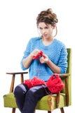 Den torterade unga flickan i en tröja sitter på en stol med ett rött garnnystan och att sticka en halsduk och en Spitz trött Vit  Arkivbilder