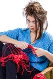 Den torterade unga flickan i en tröja sitter på en stol med ett rött garnnystan och att sticka en halsduk och en Spitz trött Vit  Royaltyfri Fotografi