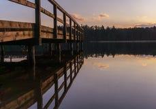 Den träbryggan eller pir reflekterade i sjön - solnedgång Royaltyfri Fotografi
