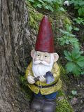 Den trädgårds- gnomen med en yxa i hans hand lutar mot en gammal trädstam Arkivfoton