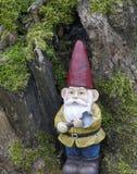 Den trädgårds- gnomen med en yxa i hans hand lutar mot en gammal trädstam Arkivbild