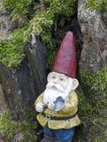 Den trädgårds- gnomen med en yxa i hans hand lutar mot en gammal trädstam Royaltyfri Bild