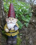 Den trädgårds- gnomen med en yxa i hans hand står i träna på en trädstubbe mellan gröna växter Arkivfoto