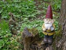 Den trädgårds- gnomen med en yxa i hans hand står i träna på en trädstubbe mellan gröna växter Fotografering för Bildbyråer