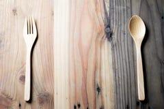 Den trägaffeln och skeden på en wood tabell Arkivbild
