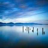 Den träpir eller bryggan återstår på en blå sjösolnedgång- och himmelreflexion på vatten. Versilia Tuscany, Italien Royaltyfri Fotografi