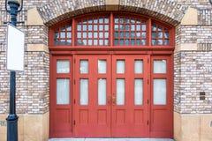 Den träröda dörren med den moderna stil- och tegelstenväggen Royaltyfria Bilder