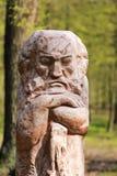 Den träsned statyn av ett mytiskt tecken för saga, parkerar landskapgarnering mot suddig bakgrund för grönska arkivbilder