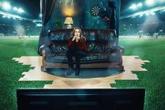 Den tråkiga fanen sitter på soffan och den hållande ögonen på TV:N i mitt av ett fotbollfält Arkivbilder
