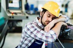 Den trötta arbetaren faller sovande under arbetstid i fabrik royaltyfria bilder