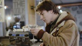 Den trötta berusade unga mannen dricker tequila och talar på telefonen i stång stock video