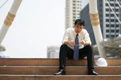 Den trötta eller stressiga affärsmannen sitter på trappan, når han har arbetat Royaltyfria Foton