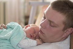 Den trötta fadern avverkar med hans nyfött behandla som ett barn sovande Royaltyfri Bild