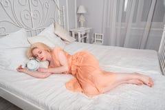 Den trötta flickan önskar att sova och ställer in larmet Arkivfoton