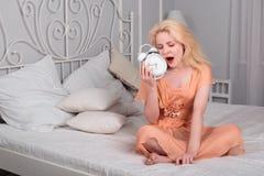 Den trötta flickan önskar att sova och ställer in larmet Fotografering för Bildbyråer