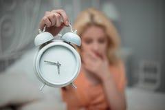 Den trötta flickan önskar att sova och ställer in larmet Royaltyfria Bilder