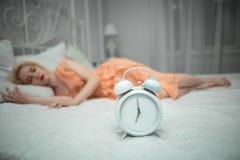 Den trötta flickan önskar att sova och ställer in larmet Arkivfoto