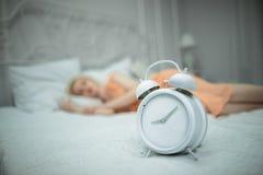 Den trötta flickan önskar att sova och ställer in larmet Royaltyfri Foto