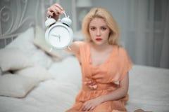 Den trötta flickan önskar att sova och ställer in larmet Royaltyfri Fotografi