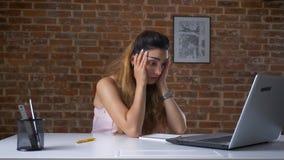 Den trötta funktionsdugliga kvinnan använder hennes bärbar dator som skriver, medan sitta på skrivbordet över tegelstenväggen, ut lager videofilmer