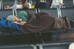 Den trötta grabben sover i flygplatsvardagsrum royaltyfri fotografi