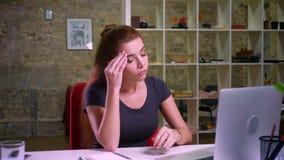 Den trötta gulliga ljust rödbrun caucasian flickan som i regeringsställning sitter och ser hennes kopplade av bärbar dator, många stock video