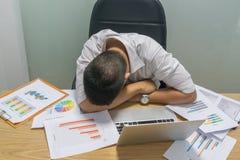 Den trötta kontorsmannen som tar kortslutning, ta sig en tupplur på arbetsplatsen arkivfoton