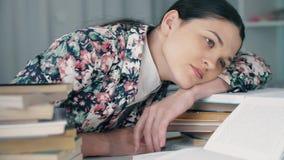 Den trötta kvinnan ligger på böcker arkivfilmer