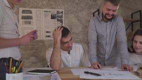 Den trötta mannen griper hans huvud, medan diskutera teckningar som arbetar på fel arkivfilmer