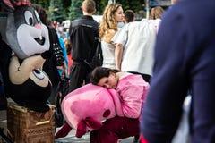 den trötta mannen i en rosa piggy dräkt sover i mitt av folkmassan Royaltyfria Foton