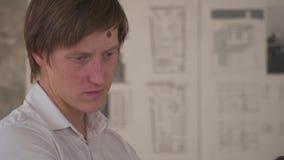 Den trötta mannen i en vit skjorta står mot bakgrunden av en teckning på väggen arkivfilmer