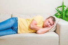 Den trötta mannen lägger ner för att ta en ta sig en tupplur på soffan Arkivfoto